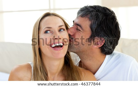 Enamoured lovers smiling in the bedroom - stock photo