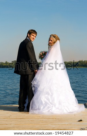 Enamoured pair in day of wedding. Ahead a new life similar to the river, with a strong current and waves