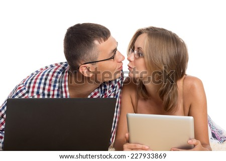 Enamoured young men kissing each other, holding laptop and Tablet PC - stock photo