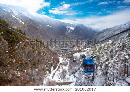 Encamp town in Andorra and cable car for lifting skiers and snowboarders to the top of the mountain - stock photo