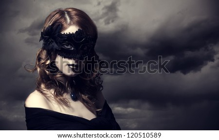 Enchantress in mask at storm sky background. - stock photo