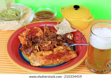 Enchiladas on colorful plate with rice and beans.  Avocado and chips and mug of frothy beer.