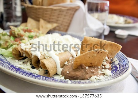 Enchiladas with cheese, beans and vegetables  - stock photo