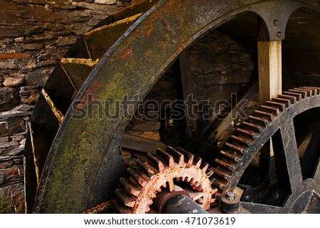 Enclosed water mill wheel workings with ancient metal and wooden cog system part of industrial heritage.