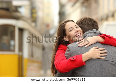 Encounter of a happy couple hugging in love in the street after a tram travel in a colorful scenery - stock photo