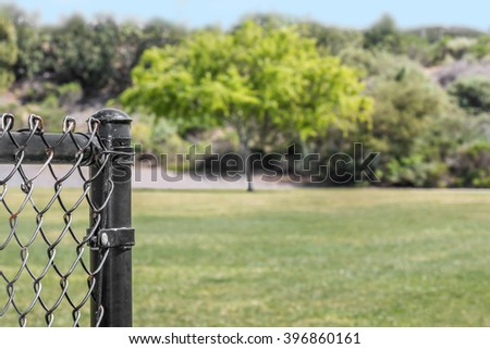 End of a black metal chainlink fence post in a public park. Grassy field and trees in blurry background. Copy space.  - stock photo