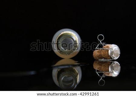 End of a party. Opened wine bottle lays on a glasses table. From her champagne flows - stock photo
