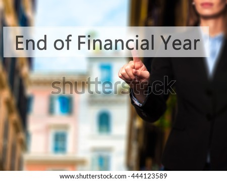 End of Financial Year - Businesswoman hand pressing button on touch screen interface. Business, technology, internet concept. Stock Photo - stock photo