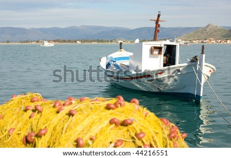 End of fishing day. White boat and yellow fishing net with clear blue sea - stock photo