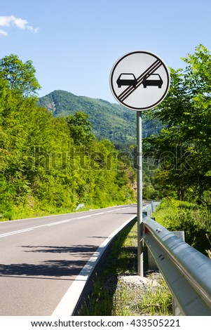 End of overtaking prohibition road traffic sign on a signpost at the side of an empty mountainous road - stock photo