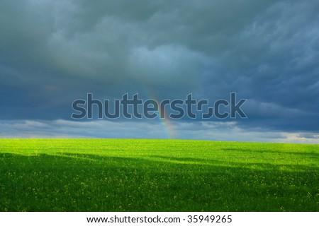 end of rainbow above the green field on a background a dark cloud
