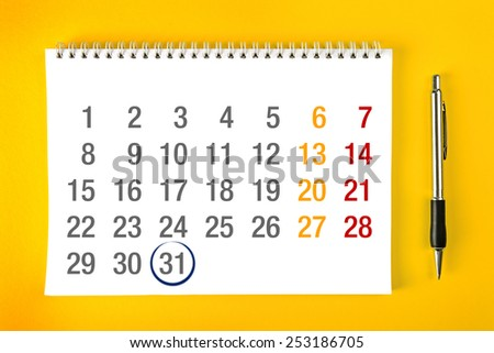 End of the month, Paper Calendar Page with Spiral Binding with pencil stroke around the last day of the month, top view. - stock photo