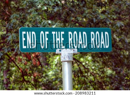 End of the Road Road humoristic and funny name of a direction corner street sign on directional traffic pole  - stock photo