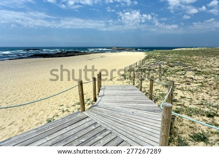 End of wooden walkway over dune giving access to a beautiful deserted beach in northern Portugal - stock photo