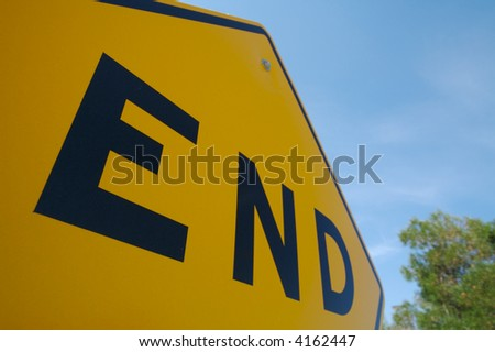 End Sign with Trees and Blue Sky - stock photo