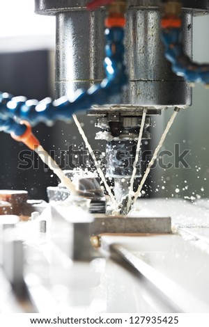 End-tooth vertical mill cutting the metal blank with cooling liquid - stock photo