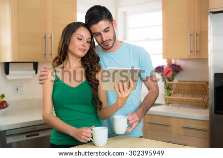 Endearing couple looking at videos online on a smart tablet sad emotional love sweet hug