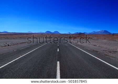 endless asphalt road up in the mountains from the plateau of san pedro de atacama to an active smokey vulcan