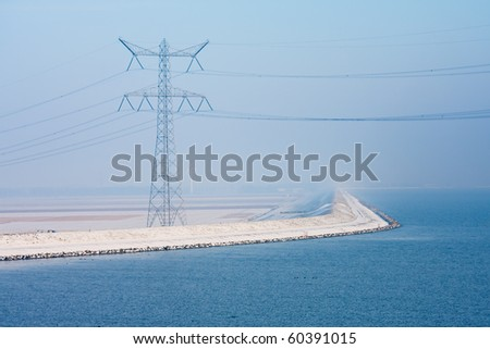 Endless Dutch snowy dike disappearing in cold winter haze - stock photo