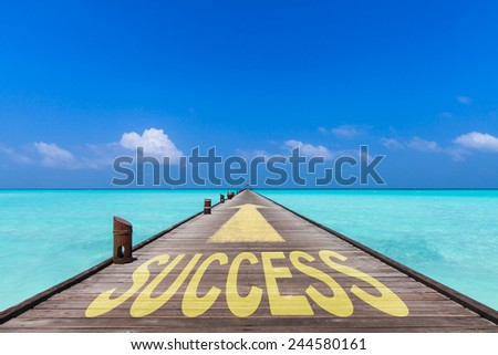 endless jetty with an yellow arrow  leading over a turquoise sea to the horizon. On the jetty is written the word success. Concept for proceeding to success.  - stock photo