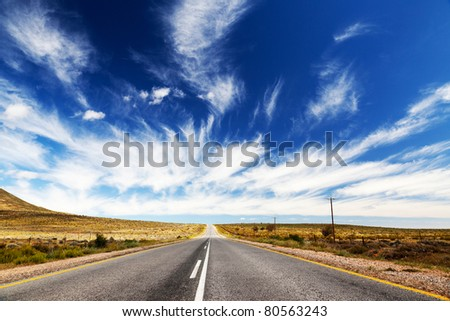 Endless, lonely road or highway, which runs towards the horizon. - stock photo