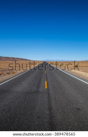 Endless open straight road in Death Valley National Park - stock photo