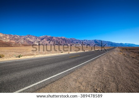 Endless open straight road in Death Valley National Park from side - stock photo