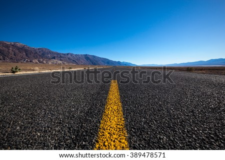 Endless open straight road in Death Valley National Park  low angle - stock photo