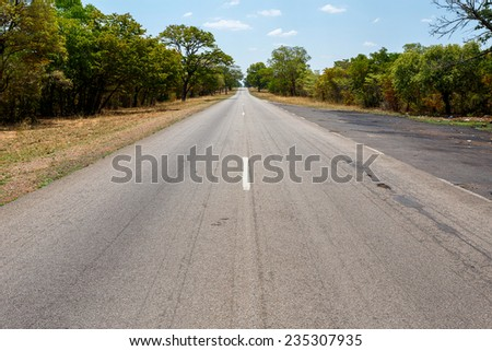 Endless road in Namibia, Caprivi Game Park, with blue sky - stock photo