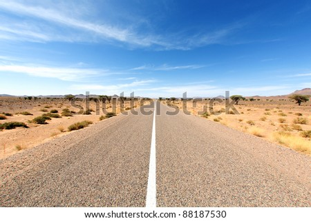 Endless road in Sahara Desert with blue sky, Africa - stock photo