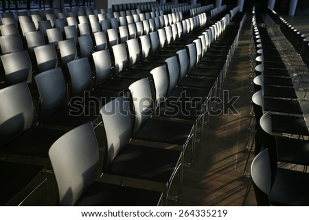 Endless rows of chairs in a modern conference hall. Rows of empty chairs prepared for an indoor event  - stock photo