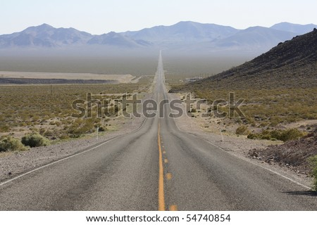 Endless straight desert highway in Death Valley, Nevada in the USA - stock photo