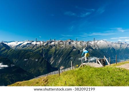 enduro bike rider starting on the high mountain technical trail in austrian alps on wildkogel im salzburg with glacier peaks view - stock photo