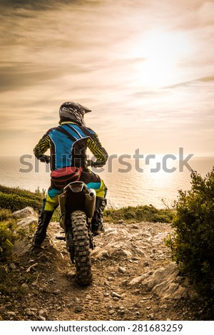 Enduro racer sitting on his motorcycle watching the sunset. - stock photo