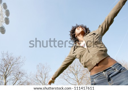 Energetic black woman with her arms outstretched against the blue sky in London city, with the London Eye appearing in the corner, smiling. - stock photo