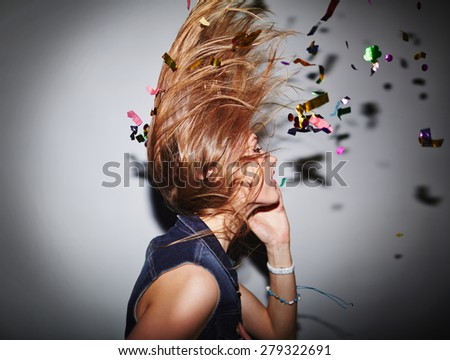 Energetic female dancer with confetti having fun in nightclub - stock photo