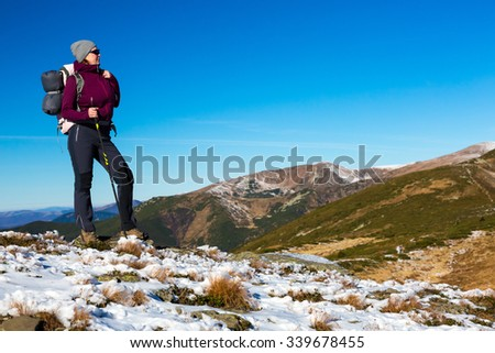 Energetic Female Hiker Staying on Snowy Terrain and Observing Scenic Mountain View Sporty Clothing Jacket and Pants Backpack and Walking Pole - stock photo