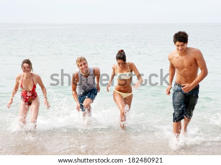 Energetic group of four friends laughing running together on the shore of a white sand beach on holiday, joyfully having fun and enjoying an exciting trip. Travel and teenagers lifestyle.