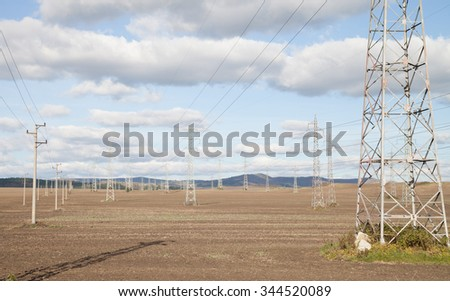 Energetic landscape - power lines high voltage against the blue sky with white clouds - stock photo