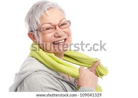 Energetic old woman smiling after workout, holding towel around neck. - stock photo