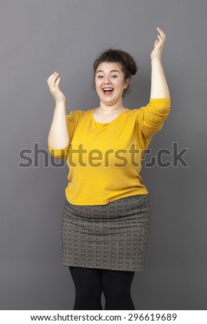 energetic 20s big woman acting thrilled, wearing colorful sweater and skirt, expressing joy and excitement with hand gesture and dance - stock photo