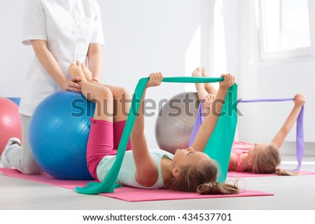 Energetic school girls exercising with resistance bands and balls with the help of an instructor - stock photo