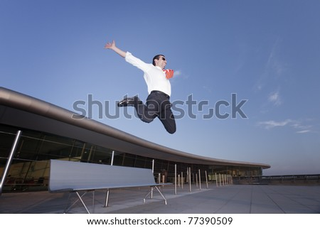 Energetic screaming business person enjoying to jump from bench symbolizing success or fun in business. - stock photo