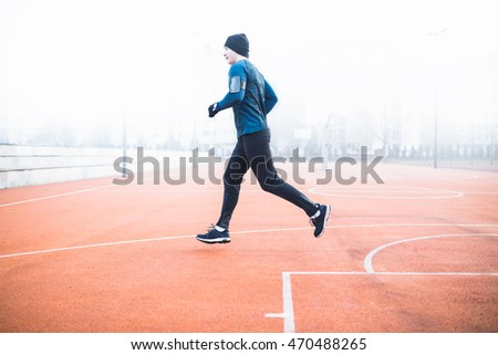 Energetic shot of a jogger. Depth of field, selective focus, warm tone filter. Intentional motion blur and color shift