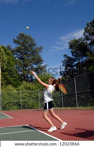 Energetic teen serves tennis ball during a high school tennis match.  Uniform is black skirt and white tee shirt. - stock photo