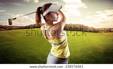 Energetic woman practicing golf exercise over beautiful landscape background. Pretty sportswoman hitting the ball with golf club. - stock photo