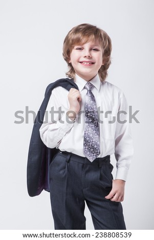 energetic young successful businessman with a jacket over his shoulder smiling and looking at the camera - stock photo