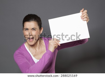 energetic young woman raising a blank communication board with good news on - stock photo