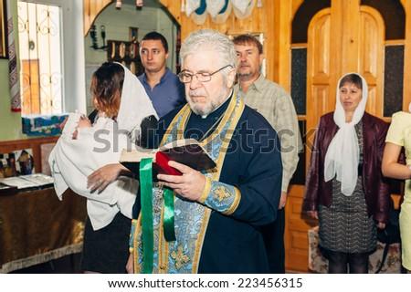 Energodar, UKRAINE - September 24, 2014: The Holy Orthodox rite of the sacrament of baptism newborn baby in a small Christian Church September 24, 2014 in Energodar, Ukraine. - stock photo