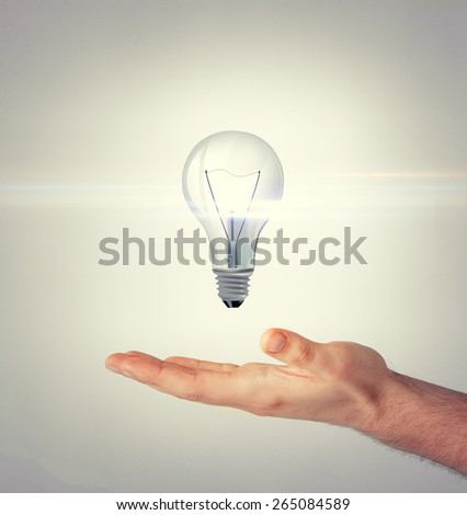 energy and environment concept - man hand with light bulb